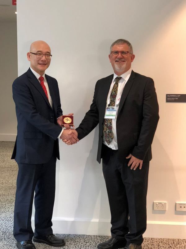 Soon Lee the Distinguished Pathologist recipient for 2018 being congratulated by IAP President Peter Bethwaite