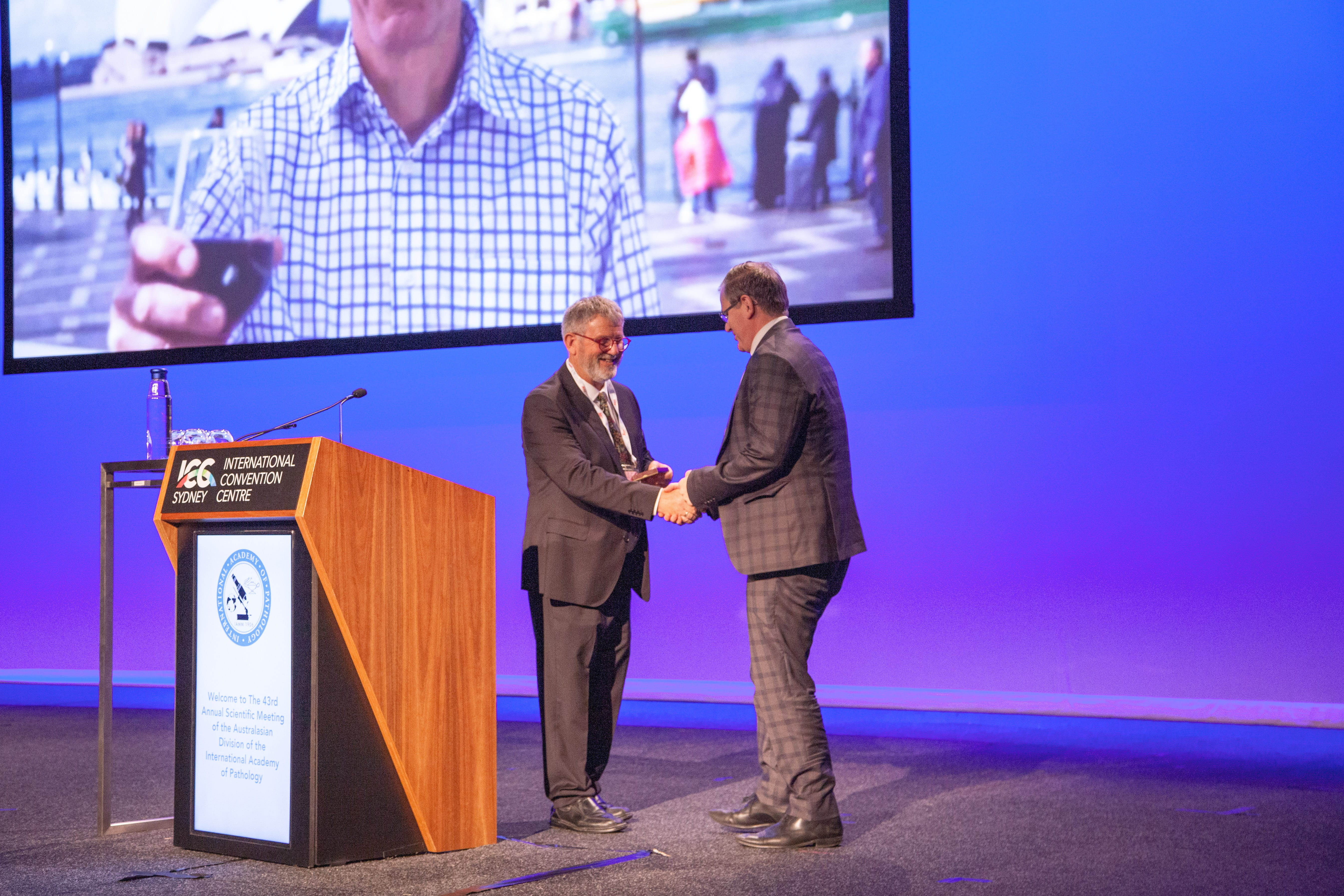 Anthony Gill accepting the Distinguished Pathologist Award on behalf of Robert Eckstein