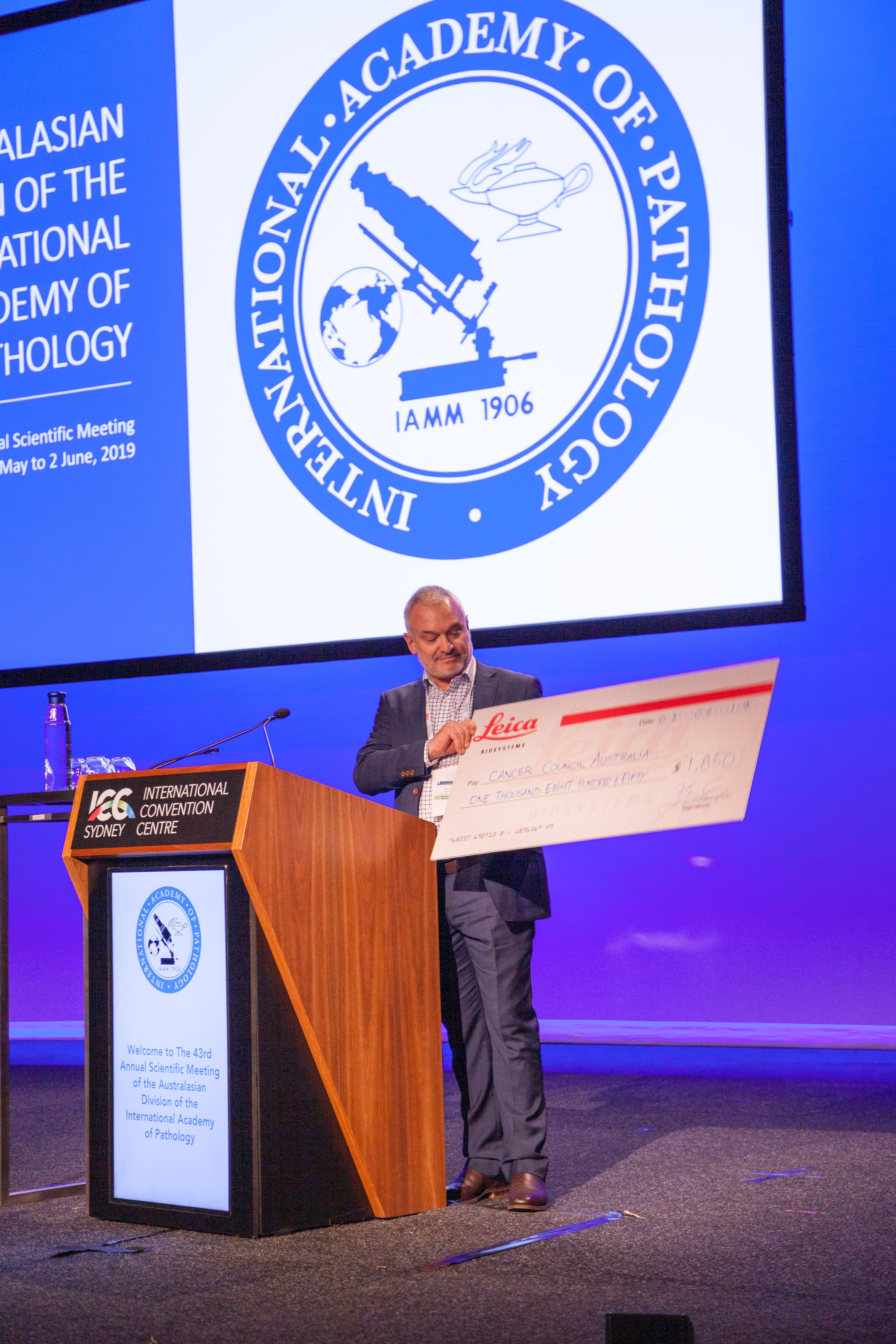 Kevin Balzarolo Leica Biosystems with a cheque for the Cancer Council Australia from funds raised at the conference
