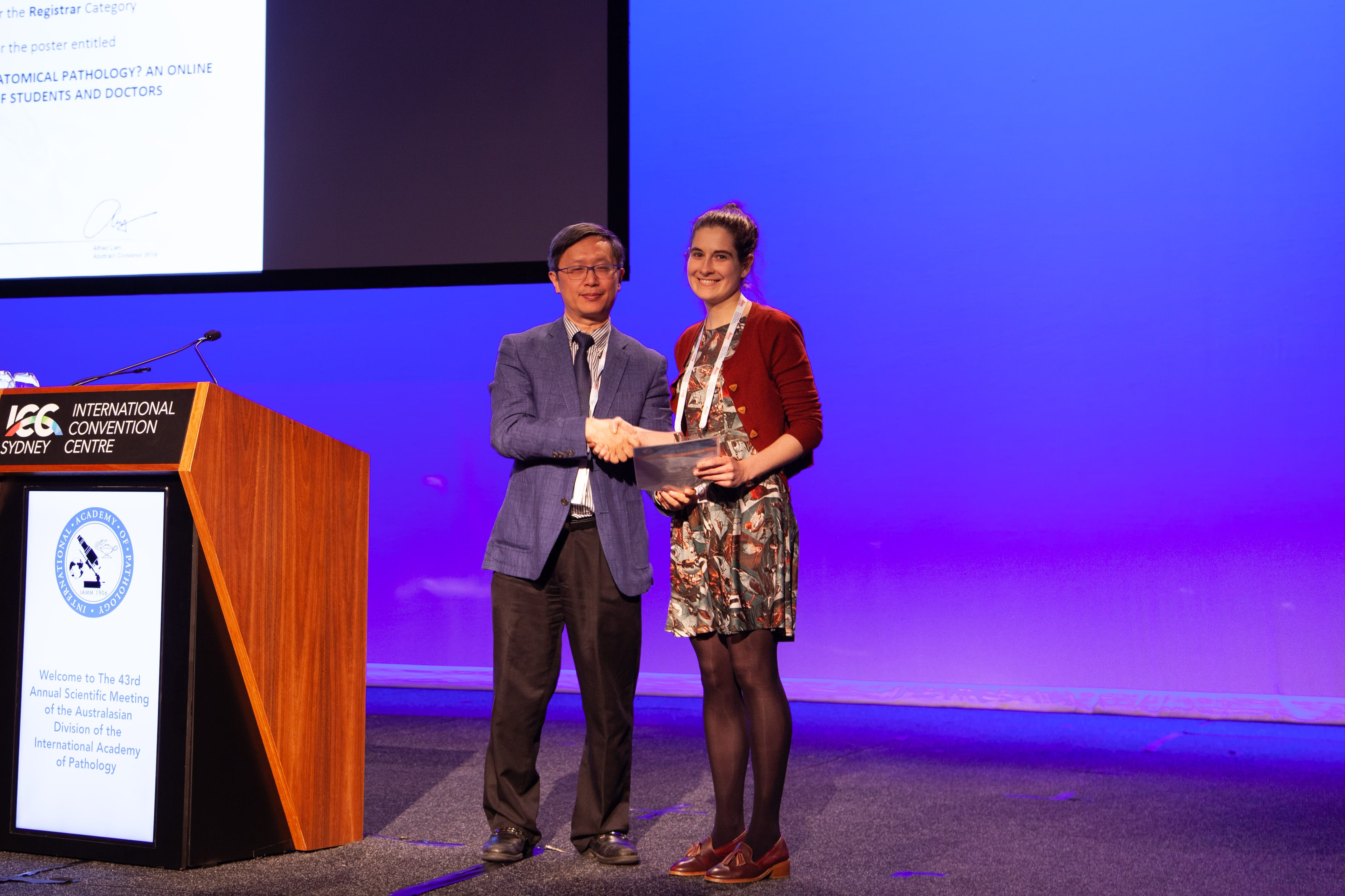 Alfred Lam presenting 2nd Commentation Prize Winner in Abstract Poster Registrar Category to Francesca Watts