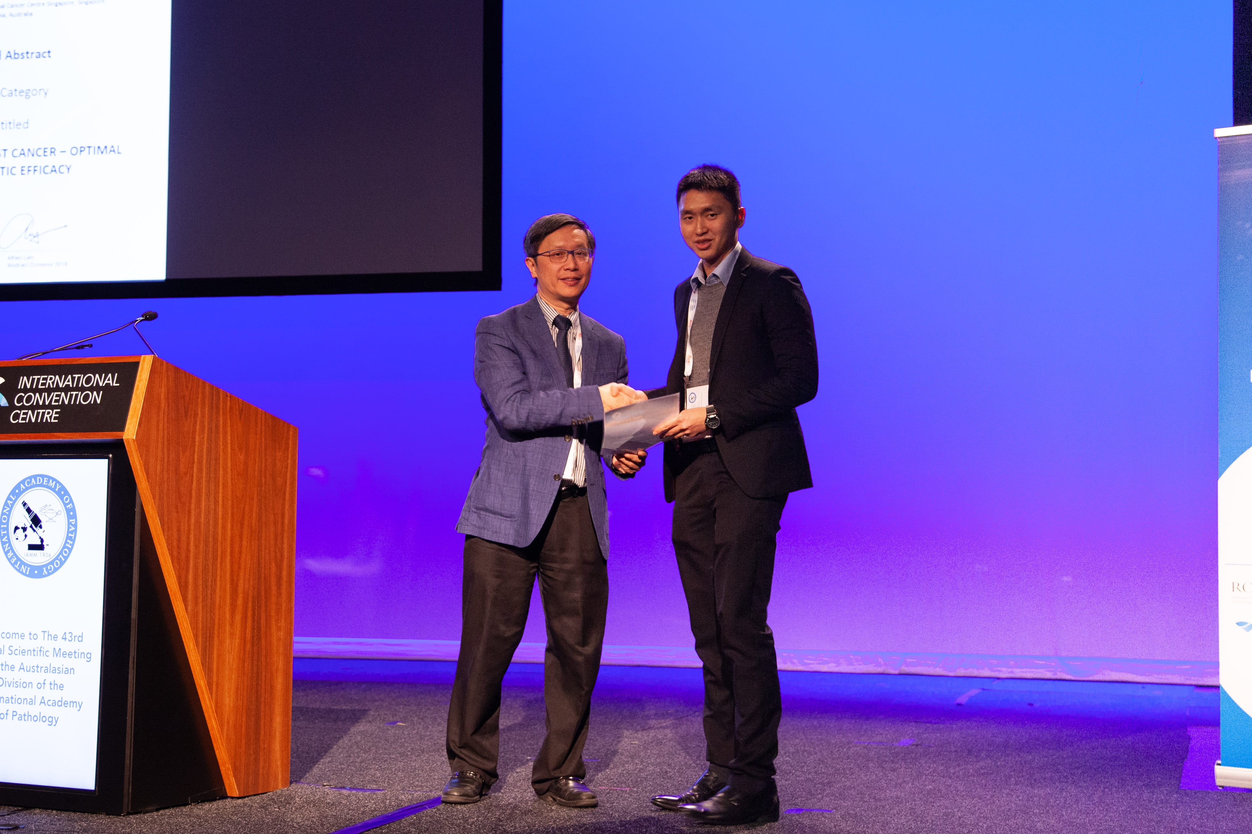 Alfred Lam presenting 1st Commentation Prize Winner in Abstract Poster Registrar Category to Zi Long Chow