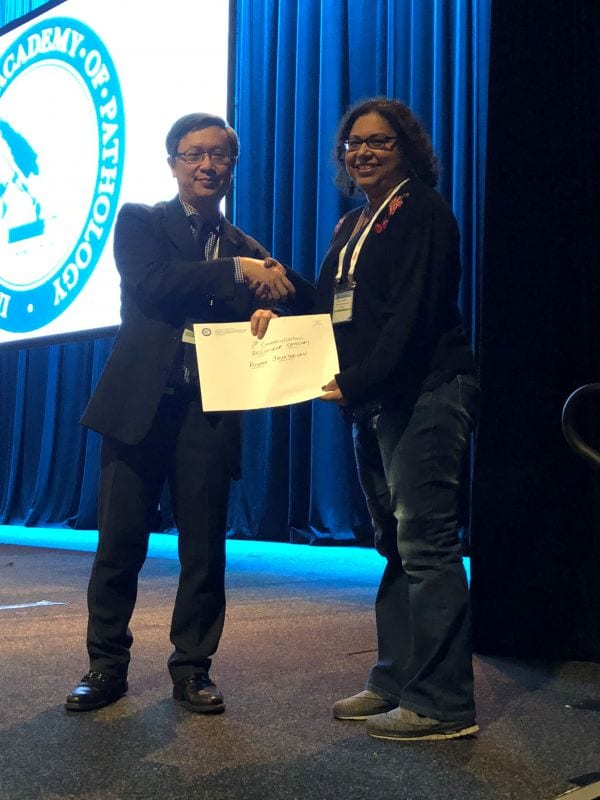 Alfred Lam presenting 1st Commendation Prize Winner in Abstract Poster Registrar Category to Roopaa Jayathevan
